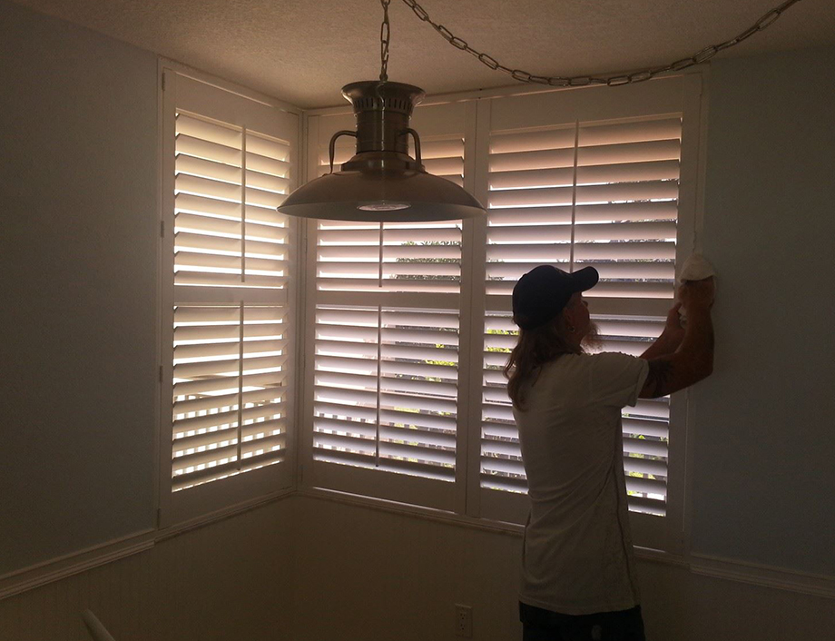 John is putting the finishing touches on some corner window Polyclad shutters